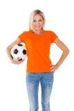 Football fan holding ball in orange tshirt Royalty Free Stock Image