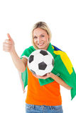 Football fan holding ball and wearing brazil flag Stock Photography