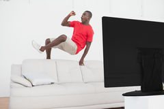 Football fan jumping over couch cheering Royalty Free Stock Images