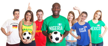 Football fan from Nigeria with ball and other fans Royalty Free Stock Image