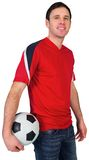 Football fan in red holding ball Royalty Free Stock Photo
