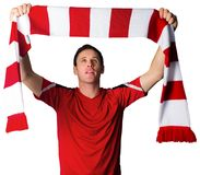 Football fan in red holding scarf Royalty Free Stock Photography