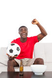 Football fan in red jersey sitting on couch cheering Stock Photography