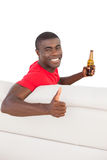 Football fan in red jersey sitting on couch holding beer showing thumbs up Stock Photography