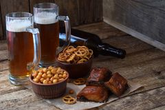 Football fan set with mugs of beer, bottle and salty snacks on wooden background. Junk food for beer or cola. Photographed with na royalty free stock photos