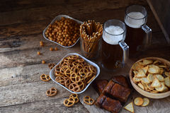 Football fan set with mugs of beer and salty snacks on wooden background. Crackers, pretzel, salted straws, nuts, dried fish. Junk Stock Photos