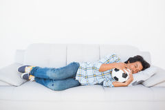 Football fan sleeping on couch hugging ball Stock Photography