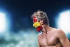 Football fan with spain flag painted on his face. In front of night stadium royalty free stock photography