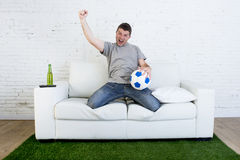 Football fan watching tv match on sofa with grass pitch carpet c Royalty Free Stock Image