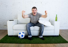 Football fan watching tv match on sofa with grass pitch carpet celebrating goal Stock Image