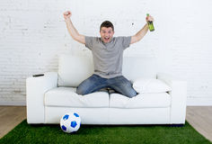 Football fan watching tv match on sofa with grass pitch carpet celebrating goal Royalty Free Stock Photos