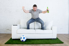 Football fan watching tv match on sofa with grass pitch carpet celebrating goal Stock Photography