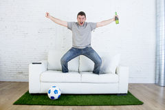 Football fan watching tv match on sofa with grass pitch carpet celebrating goal. Crazy football fan watching television soccer match celebrating scoring goal Royalty Free Stock Images