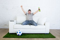 Football fan watching tv match on sofa with grass pitch carpet celebrating goal Royalty Free Stock Photography