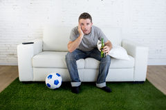 Football fan watching tv match on sofa with grass pitch carpet i Royalty Free Stock Images