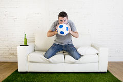 Football fan watching tv match on sofa with grass pitch carpet i. Crazy football fan cheering watching television soccer match suffering stress nervous and Royalty Free Stock Photography