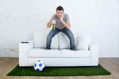 Football fan watching tv match on sofa with grass pitch carpet in stress Stock Photos