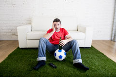 Football fan watching tv sitting off couch on grass carpet with ball emulating stadium pitch Royalty Free Stock Image