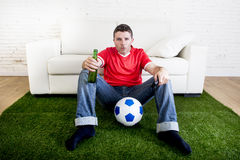 Football fan watching tv sitting off couch on grass carpet with Royalty Free Stock Images