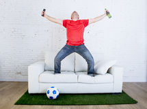 Football fan watching tv soccer celebrating goal in couch on grass carpet emulating stadium pitch Stock Image