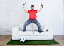 Football fan watching tv soccer celebrating goal in couch on grass carpet emulating stadium pitch Stock Photography