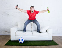 Football fan watching tv soccer celebrating goal in couch on grass carpet emulating stadium pitch. Crazy football fan in red team jersey cheering happy watching Royalty Free Stock Image