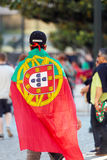 Football fan wearing a Portuguese national flag during the Euro 2016 Final. Portuguese supporter wearing a national flag before the final match between France stock images