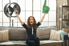 Football fan woman watching tv in loft apartment and rejoicing Royalty Free Stock Image