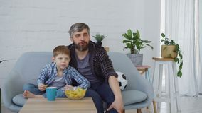 Football fans bearded man and his little child are watching match on TV at home, celebratong goal and eating crisps