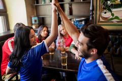 Football fans with beer celebrating victory at bar. Sport and entertainment concept - happy football fans or friends drinking beer, making high five and stock photos
