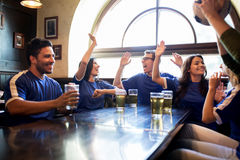 Football fans with beer celebrating victory at bar. Sport, people, friendship and entertainment concept - happy football fans or friends drinking beer, making royalty free stock photos