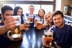 Football fans clinking beer glasses at sport bar. Sport, soccer, people and leisure concept - happy friends or football fans clinking beer glasses and Stock Photography