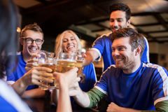 Football fans clinking beer glasses at sport bar. Sport, soccer, people and leisure concept - happy friends or football fans clinking beer glasses and Royalty Free Stock Photo