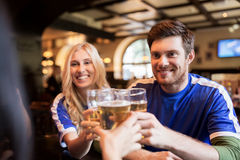 Football fans clinking beer glasses at sport bar. Sport, soccer, people and leisure concept - happy friends or football fans clinking beer glasses and Royalty Free Stock Images