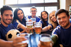 Football fans clinking beer glasses at sport bar. Sport, soccer, people and leisure concept - happy friends or football fans clinking beer glasses and Royalty Free Stock Image