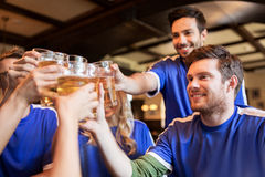 Football fans clinking beer glasses at sport bar. Sport, soccer, people and leisure concept - happy friends or football fans clinking beer glasses and Stock Images