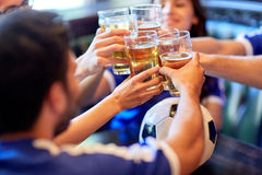 Football fans clinking beer glasses at sport bar. Sport, soccer, people and leisure concept - happy friends or football fans clinking beer glasses at bar or pub stock photo