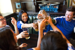 Football fans clinking beer glasses at sport bar. Sport, soccer, people and leisure concept - happy friends or football fans clinking beer glasses at bar or pub stock photography