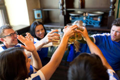 Football fans clinking beer glasses at sport bar. Sport, soccer, people and leisure concept - happy friends or football fans clinking beer glasses at bar or pub royalty free stock photography