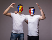 Football fans of France and Romania national teams friendly suport together the game of their teams Royalty Free Stock Image