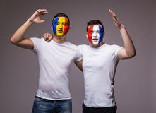 Football fans of France and Romania national teams friendly suport together the game of their teams at open match Stock Photos