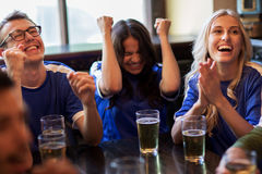 Football fans or friends with beer at sport bar. Sport, people, leisure, friendship and entertainment concept - happy football fans or friends drinking beer and stock photos