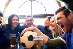 Football fans or friends with beer at sport bar. Sport, people, leisure, friendship and entertainment concept - happy football fans or friends drinking beer and royalty free stock image