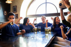 Football fans or friends with beer at sport bar. Sport, people, leisure, friendship and entertainment concept - happy football fans or friends drinking beer and Stock Photography