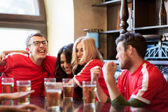 Football fans or friends with beer at sport bar. Sport, people, leisure, friendship and entertainment concept - happy football fans or friends drinking beer and Stock Image