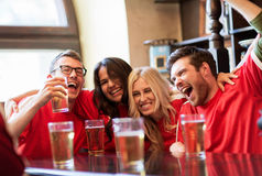 Football fans or friends with beer at sport bar. Sport, people, leisure, friendship and entertainment concept - happy football fans or friends drinking beer and royalty free stock photo