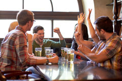 Football fans or friends with beer at sport bar. Sport, people, leisure, friendship and entertainment concept - happy football fans or friends drinking beer and Stock Images