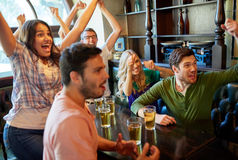 Football fans or friends with beer at sport bar. Sport, people, leisure, friendship and entertainment concept - happy football fans or friends drinking beer and royalty free stock images