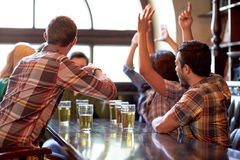 Football fans or friends with beer at sport bar. Sport, people, leisure, friendship and entertainment concept - happy football fans or friends drinking beer and Stock Photo