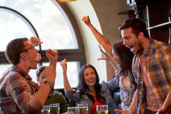 Football fans or friends with beer at sport bar. Sport, people, leisure, friendship and entertainment concept - happy football fans or friends drinking beer and Royalty Free Stock Photography